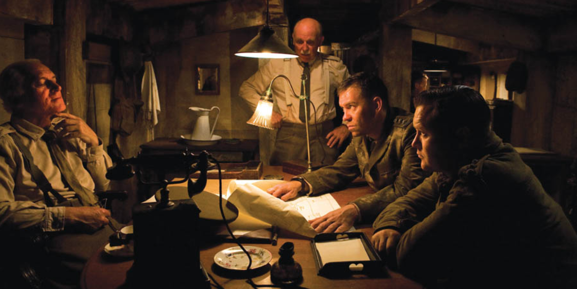 Soldiers standing around a table in a scene from the World War I movie Beneath Hill 60