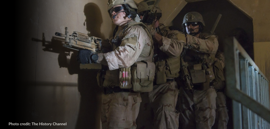3 US Special Forces soldiers inch along the wall of a building