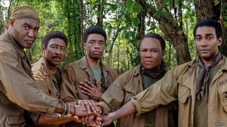 5 actors high five in a scene from Da 5 Bloods