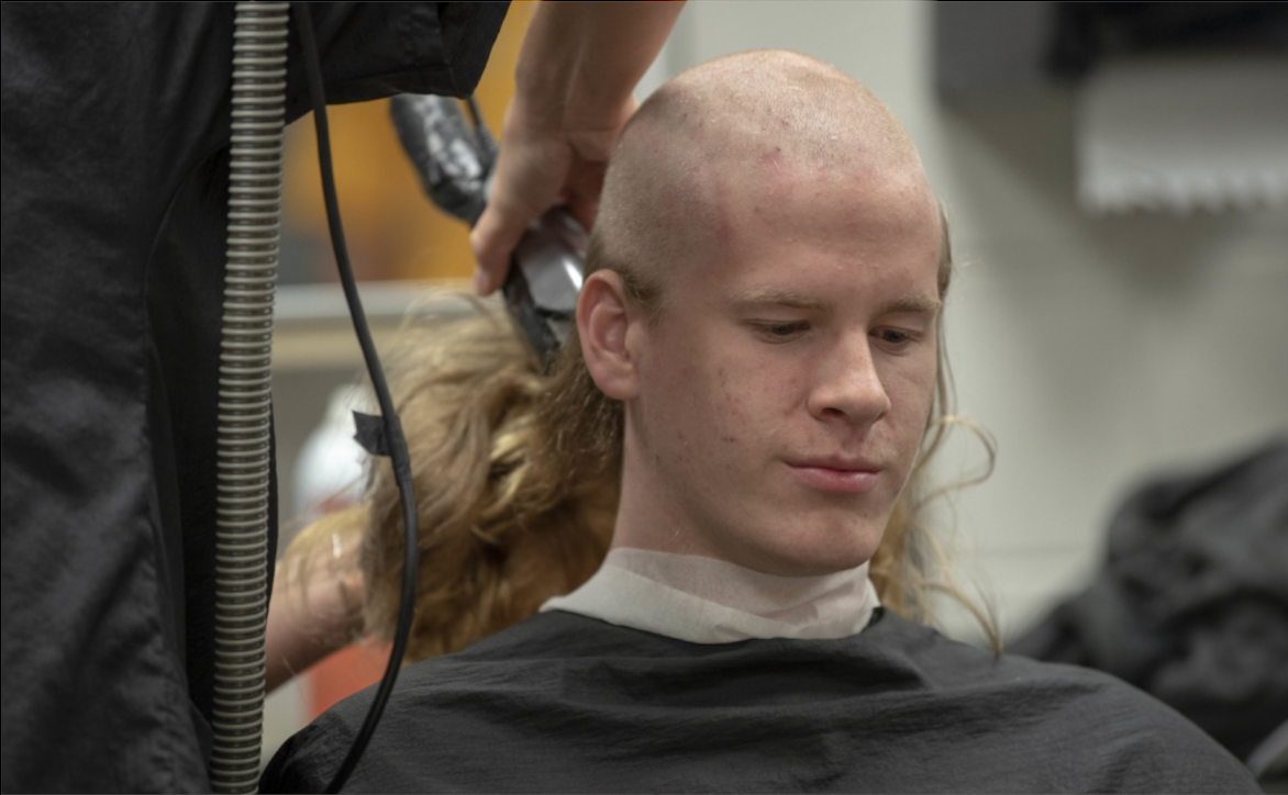 Long-haired recruit getting a buzzcut at U.S. Navy bootcamp