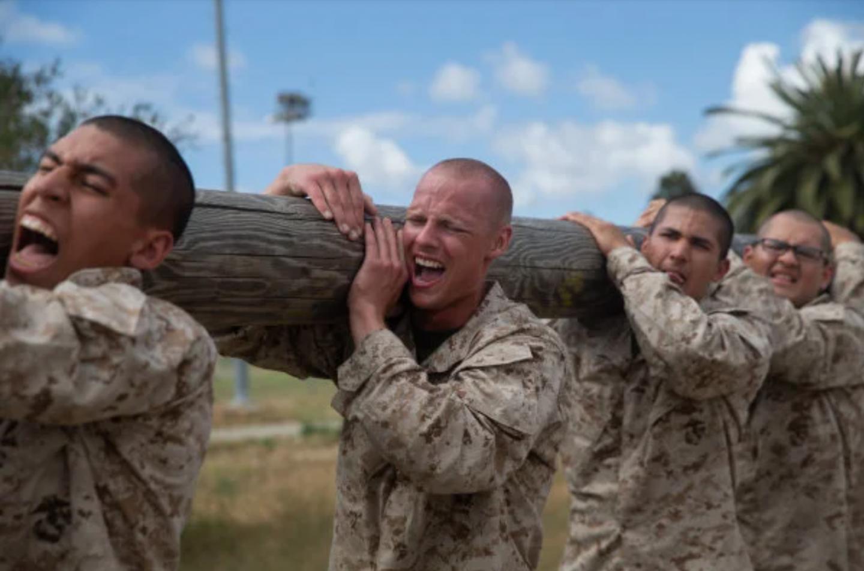 Marine recruits team up to carry a telephone pole