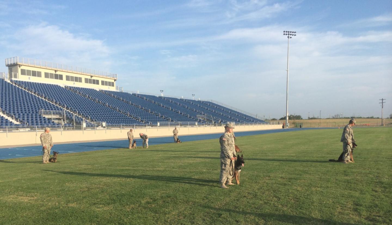 U.S. Army K9 handlers practice in a football stadium
