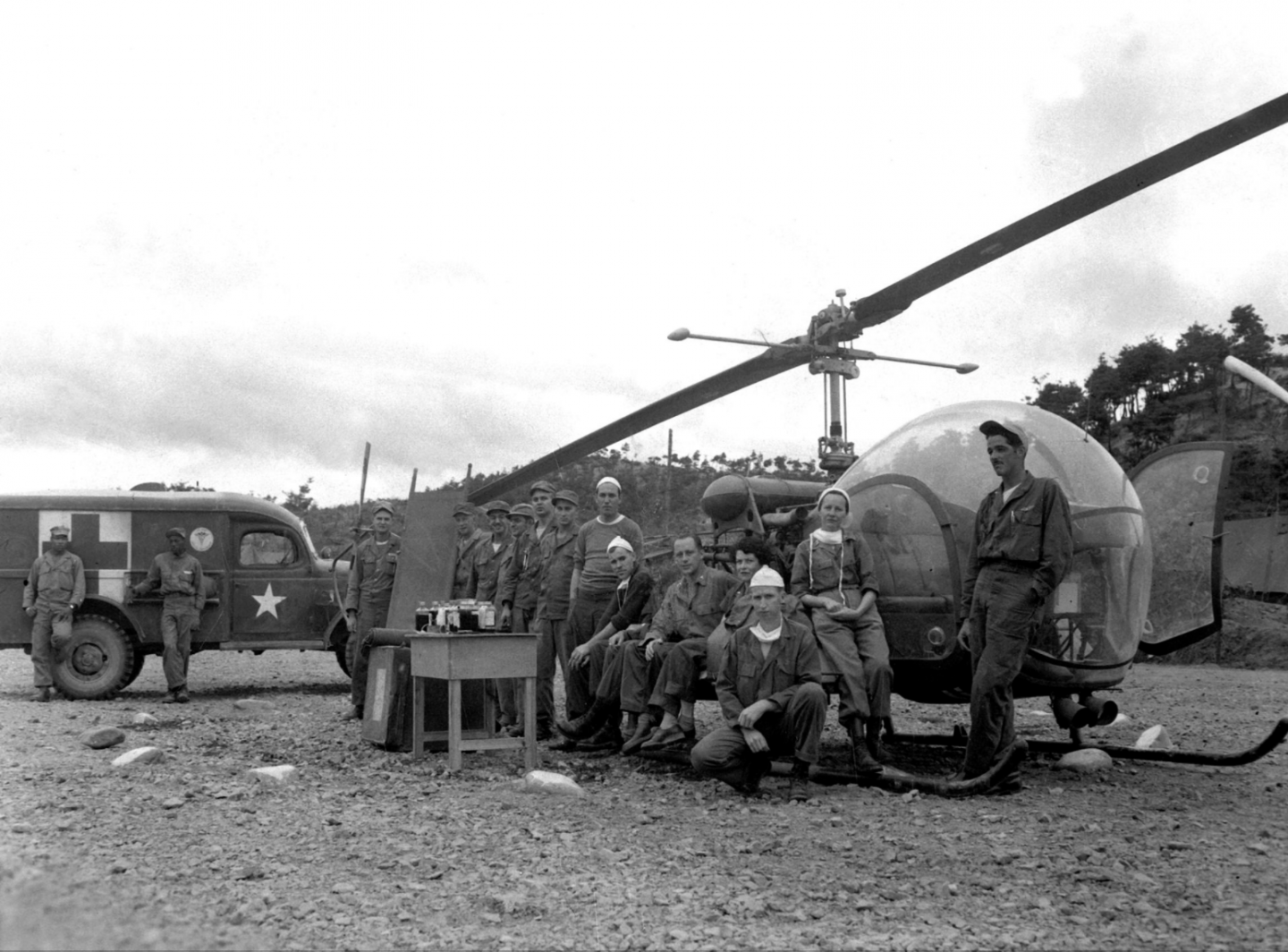 MASH Unit doctors pose with Jeep and helicopter during Korean War